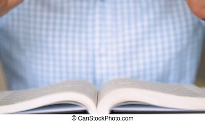 Man takes his glasses and reads a book close up - Man takes...