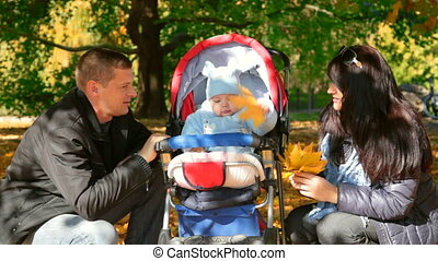 Young Happy Family with baby in a stroller on a walk in the...