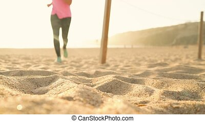 Running shoes - woman tying shoe laces on sandy beach at sunset. Slow motion