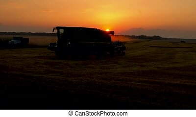 Harvesting machinery leaves field after harvest at sunset....