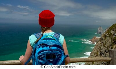 Woman with a backpack enjoys a view of the ocean coast near...