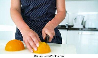 Woman cutting orange in a modern kitchen