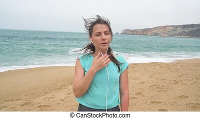 Woman on beach listening to music on headphones from smart phone. Nazare, Portugal. Slow motion