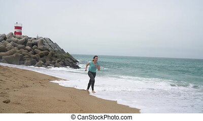 Athletic woman running along the beach