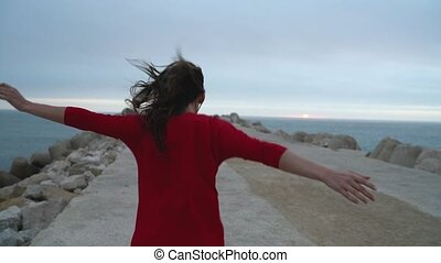 Woman in red dress runs to the lighthouse on the ocean coast