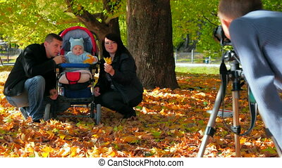 son makes a photo of his family in the park