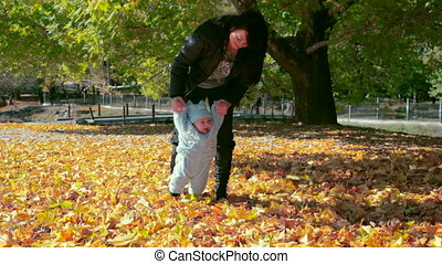 Mother and baby on fallen leaves in the park
