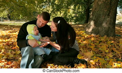 happy family in the park - Happy Family Holding Their Child