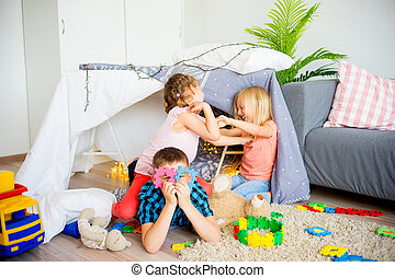 Kids in a wigwam - Three kids playing together in a wigwam...
