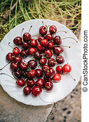 Group od delicious fresh cherries on white plate