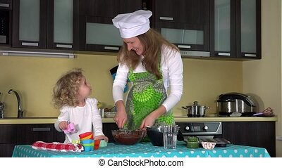family girls cook food in kitchen. Happy girl with mother mix batter in bowl