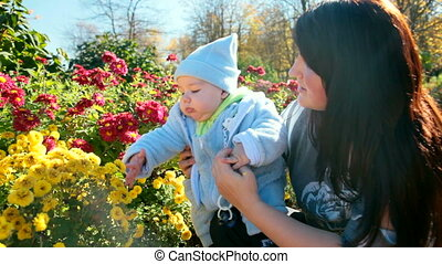 mother and baby near a flowerbed - Smiling mother and child...