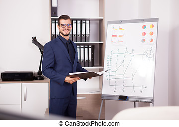 Young smiling businessman with a folder with charts in hands nex