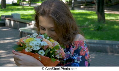 Young beautiful woman admiring a bouquet of flowers. Flowers...