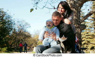 family with toddler looking at the cat on a bench in autumn...