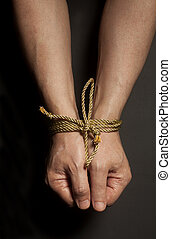 Male hands bound with rope