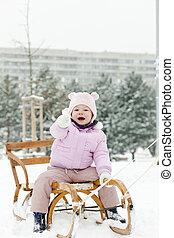 little girl sledding in snow