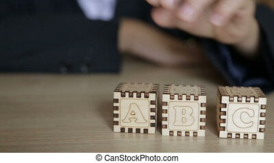 The boy folds cubes with English letters