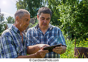 The old and young farmer are discussing about the harvest....