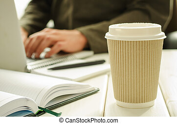 Paper cup of coffee on work-table with office stuff,...