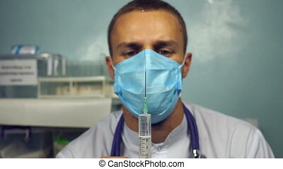 Medical worker preparing syringe for injection. Portrait of young male caucasian doctor in mask pouring a liquid from a syringe.Medicine heath care concept. Slow motion Close up