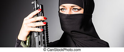 Woman holding an automatic weapon close-up - Woman holding...
