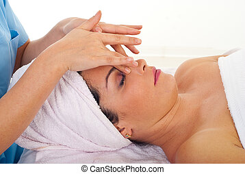 Woman relaxing with facial massage - Woman receiving a...