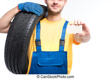 Worker holds tire and empty businesscard in hands - Tyre...