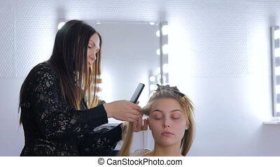 Hairdresser using straightener on long hair of client in...