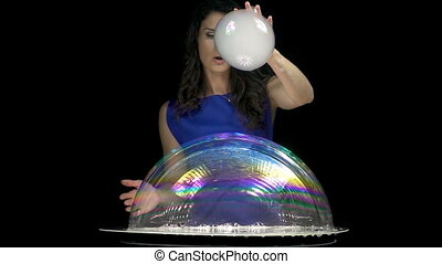 Attractive brunette girl mixing soap bubbles on black...