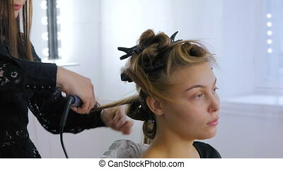 Professional hairdresser doing hairstyle for woman - making...
