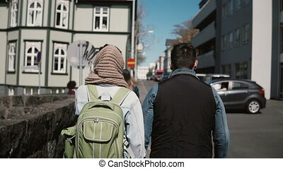 Back view of young stylish couple walking in downtown...