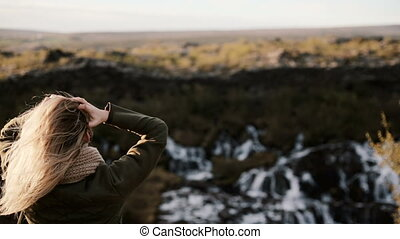 Back view of young blonde woman standing on the cliff and looking at Barnafoss waterfall in Iceland, touching hairs.