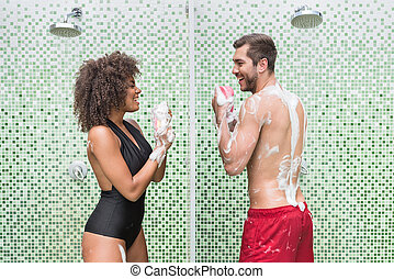 Happy youthful couple having fun while washing indoor -...
