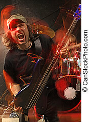 Heavy metal bass guitar player - Bass guitarist playing on a...