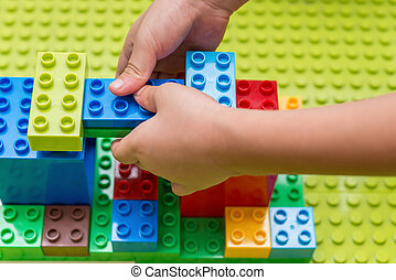 kid playing colorful toy blocks