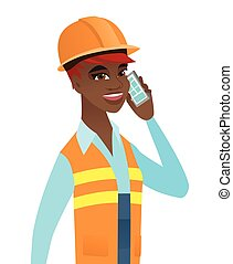 Young african builder talking on a mobile phone.