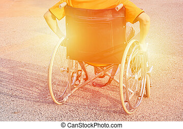 man hand on wheel of wheelchair at road in the city park use us insurance patient disability concept image warm tone effect