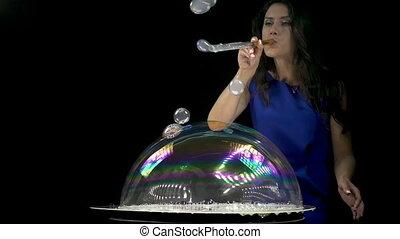 Beautiful brunette girl blowing soap bubbles
