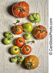 Ripe and unripe tomatoes on wooden table
