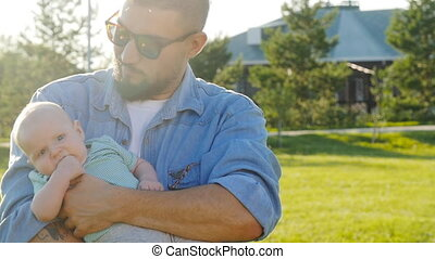 Happy father holding his son at sunset in the park
