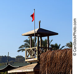 tower of lifeguard with red flag on the beach
