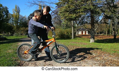 father teaches his son to ride a bicycle in the park
