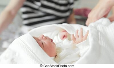 Maternity hospital - employee of the hospital is swaddling a...