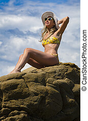 Young girl sitting on the rock tanning - Young girl with...