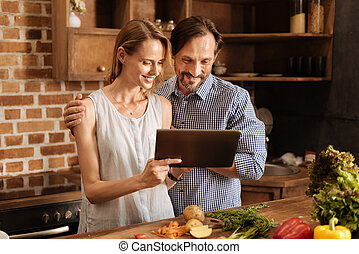 Charming lovely couple reading cooking instructions - Lets...