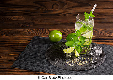 A green mojito with a straw. A mojito cocktail on a wooden background. Mint, ice and carambola on an alcoholic drink. Copy space.
