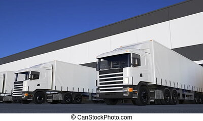 White freight semi trucks loading or unloading. Road cargo transportation. Seamless loop 4K clip