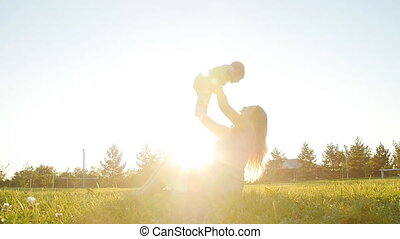 A young mother holding a little son in her arms at sunset