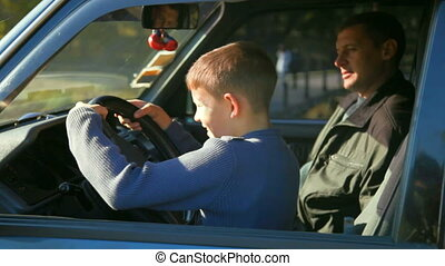 father and son in the car - father teaches son to drive car